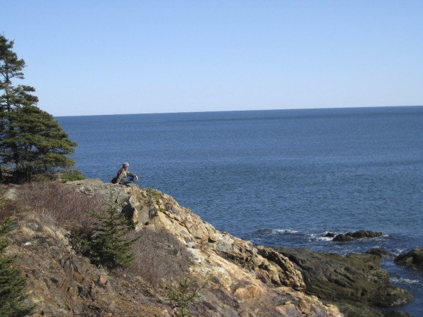 An unidentified hiker takes in the view on the Great Head Trail in Acadia NP on a spectacular early spring day.
