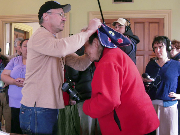 Donald Soctomah, Passamaquoddy historian and former tribal representative in the Maine legislature, places a traditional Maliseet woman's peaked hat on the head of Ojibway elder Josephine Mandamin as she prepares to lead the walkers from the East in the 2011 Mother Earth Water Walk from Machias, Maine, to Bad River, Wisconsin. Photo by Kathryn Olmstead.