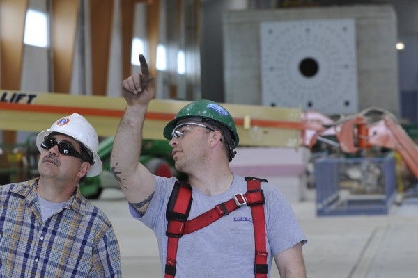 Peter Harper (right) an installer of PDQ Door in Hampden,  points to spring and couterbalance mechanism as he talks with PDQ Door vice president Kerry Fifer (left) as they work to install a sectional door at the  soon-to-be-completed Advanced Nanocomposites in Renewable Energy Laboratory at the University of Maine in Orono Friday, May 13, 2011. Once completed later this summer, the laboratory will boast the longest wind testing floor in the U.S.