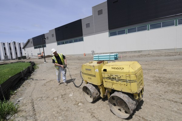 Ron Richardson of Sebec, an employee of the Sargent Corporation, uses a compactor to grade the outside of the soon-to-be-completed Advanced Nanocomposites in Renewable Energy Laboratory at the University of Maine in Orono on Friday, May 13, 2011. Once completed later this summer, the laboratory will boast the longest wind testing floor in the U.S. The large black panels on the south side of the building (seen in the background of the photo) are air solar collectors to help heat the interior of the building during the cold months.