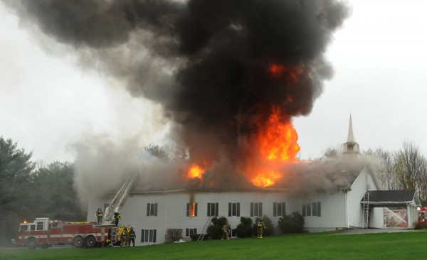 The Calvary Apostolic Church in Winterport is seen in flames as firefighters collect equipment and pull back when the roof collapsed on Thursday, May 5, 2011. One person is confirmed dead due to the blaze.