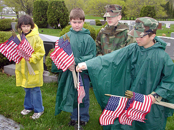 Sarah Nouhan, 10, of Connor (from left); Tierann Barbosa, 9, of Caribou; and Kyle Kilcollins, 13, of Westfield watch as Alex Kaiser, 11, of Ashland places a flag near the headstone of a veteran at Fairmount Cemetery in Presque Isle on May 21. The members of County Patriots Young Marines assisted the Presque Isle VFW in preparing veterans' graves for Memorial Day.