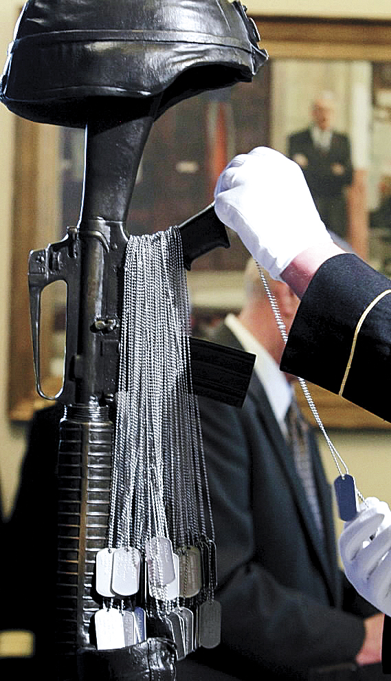 Dog tags are placed on the Battlefield Cross Memorial during a ceremony to honor Mainers who gave their lives in Iraq and Afghanistan, at the State House in Augusta, Maine on Wednesday.