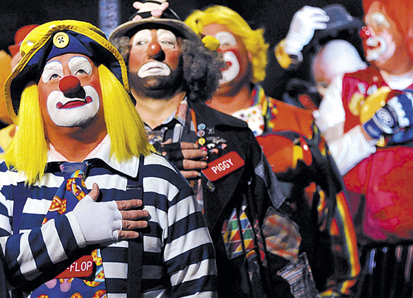 Flip-Flop (left), Piggy and other Anah Shrine clowns stand at attention on Friday as Stephanie Erb (not pictured) of Brewer sings the national anthem at the start of the Anah Temple Shrine Circus' afternoon show at Bangor Auditorium. The annual fundraiser held shows through Sunday.