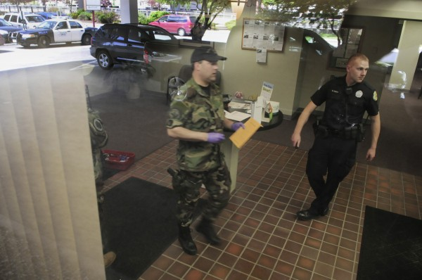 Bangor police Patrolman Jim Hassard and Bangor police Officer Brian Smith (right) assist fellow officers while talking with bank personnel (not pictured) after a report of a robbery at Penobscot County Federal Credit Union at 1 Merchants Plaza in downtown Bangor on Wednesday, May 25, 2011.