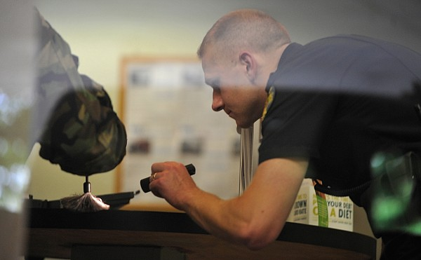 Bangor police Officer Brian Smith (right) shines his flashlight on the customer counter as Bangor police Patrolman Jim Hassard (hand and brush on left) dusts for fingerprints after a reported robbery at Penobscot County Federal Credit Union at 1 Merchants Plaza in downtown Bangor on Wednesday, May 25, 2011.