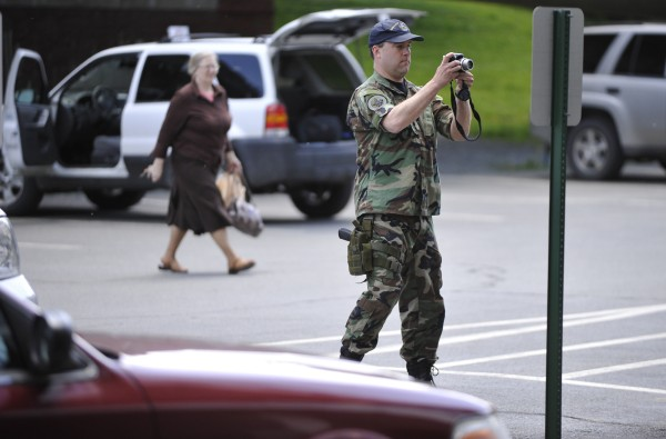 Bangor police Patrolman Jim Hassard takes exterior photos of Penobscot County Federal Credit Union in downtown Bangor after a robbery was reported there Wednesday, May 25, 2011.