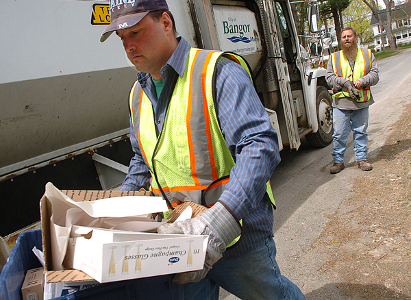 Bangor Public Works Department employees Jerry Maynard, foreground, and Rick LeGasse, background, pick up recyclable materials as part of the city's curbside recycling program on Monday. Despite opposition from some residents, the Bangor City Council is exploring the possibility of implementing single-stream recycling and pay-as-you-go trash removal.