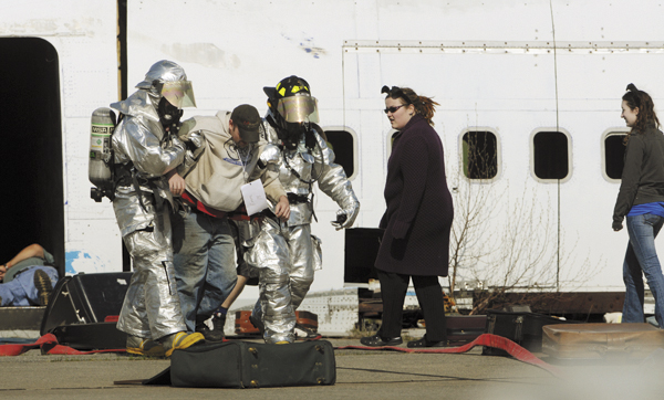 Bangor International Airport firefighters help a victim of a mock air disaster to an awaiting ambulance as females wearing fake ears roam the area acting as aggressive dogs on Saturday at the Bangor Internatinal Airport.
