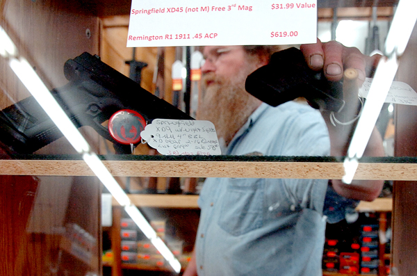 Rick Lozier, manager of Van Raymond Outfitters shows one of the small hand guns on sale in the Brewer store. State legislature hearings on several bills concerning guns are expected to be postponed until the next legislative session due to the recent incident involving State Representative Frederick Wintle. &quotPeople aren't feeling safe,&quot Lozier said about the increase in gun ownership and also stated that the regulations surrounding concealed weapons should be loosened. &quotAny law-abiding citizens should be allowed to carry a gun without any kind of concealed-weapons permit,&quot he concluded.