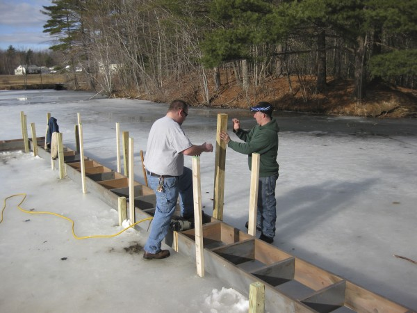 Louie Dubois and Seacoast Dock Dogs members build a dock and catwalk on the ice.