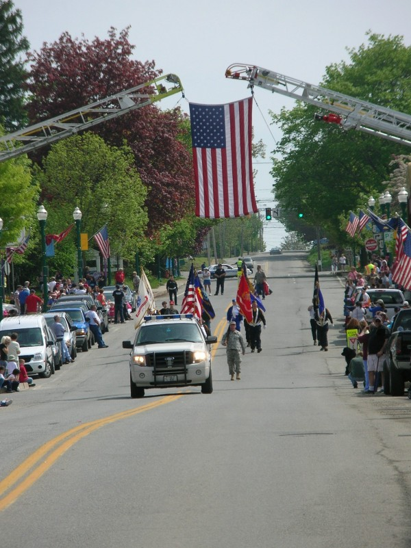 The Ellsworth Memorial Day parade proceeds down Main Street Monday underneath an American flag suspended from two ladder trucks.