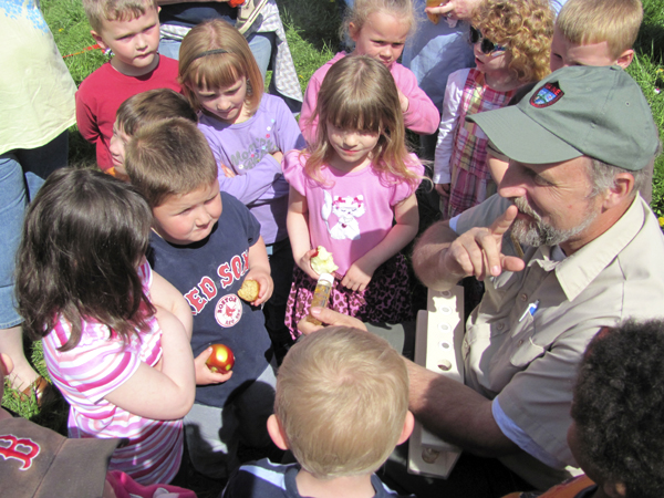 Gene Arsenault, right, a fish culture supervisor for the Maine Department of Inland Fisheries and Wildlife, shows a group of children some samples of fish eggs in various stages of development on Friday in Skowhegan.