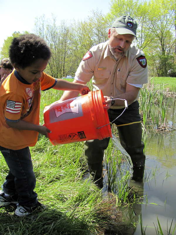 Five-year-old Ari Abruzzese of Canaan releases two brook trout into Hight Pond near downtown Skowhegan on Friday. Assisting Abruzzese is Gene Arsenault, a fish culture supervisor for the Maine Department of Inland Fisheries and Wildlife's Embden hatchery.