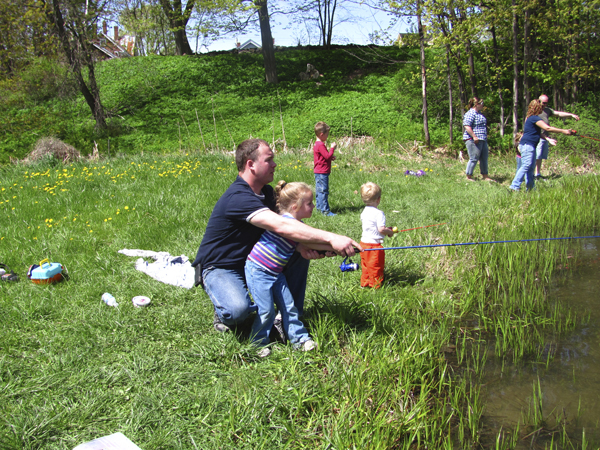 David Getchell of Cornville helps his 5-year-old daughter, Kaysie, cast a line into Hight Pond in Skowhegan during a fish-stocking demonstration Friday in Skowhegan. It was one of Kaysie's first times fishing.