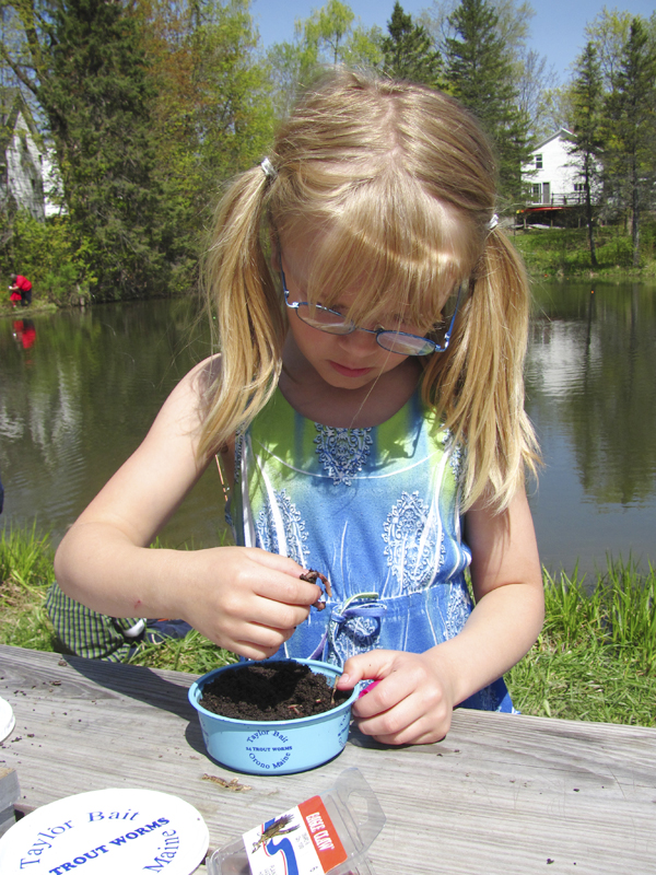 Six-year-old Sumyr Taylor of Canaan has no problem rooting worms out of a container Friday during a Hooked on Fishing event on Hight Pond in Skowhegan.