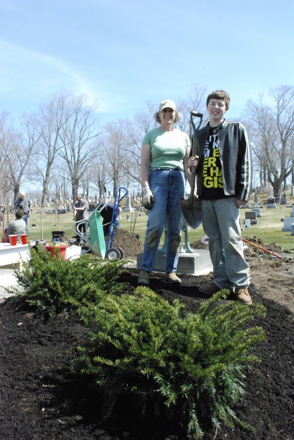 Belfast Garden Club President, Diane Allmayer-Beck and Game Loft volunteer Clayton Martin plant new shrubs in front of Belfast's Grove Cemetery on Earth Day