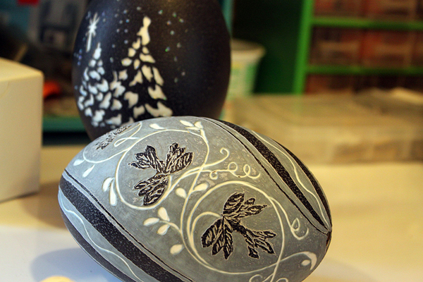 Georgette Kanach of Gray carves emu eggs, which she purchases online. The outer shell of the emu eggs are dark green, the second layer is light green, and the third layer is white, so she uses the eggs natural colors to create detailed scenes. Unfortunately, emu eggs aren't as thick as ostrich eggs, so it takes a practiced hand to work with the layers.