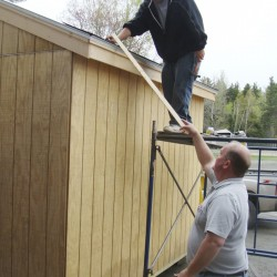 Volunteer Larry Farrington of Big Moose Township assists Jeremy St. Louis, a Greenville High School student in the JMG program, who was working on the roof of a storage shed on Friday. The shed was constructed by the students under the direction of Farrington and has been sold.