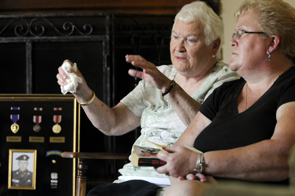 Helen Hardy (center) shares fond memories of her late husband, Capt. Herbert F. Hardy Jr., as one of her daughters, Christine Brochu, right, and other family members listen. In March 1964 Capt. Hardy was killed in action on the Cambodian border while serving in Vietnam. Behind them is a shadow box with his medals and portrait.  Capt. Hardy is one of many Maine soldiers that will be honored on Memorial Day. Photographed during a family gathering at Helen Hardy's house in Brewer Thursday, May 27, 2011.