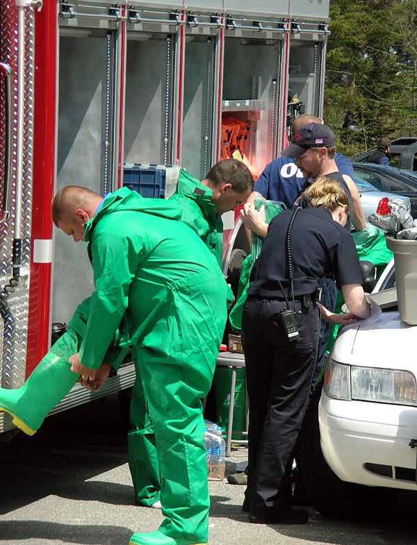 Members of the Orono-Old Town Regional Rapid Response Team suit up Thursday before they enter the Bar Harbor Bank and Trust operations center in Ellsworth. The building was evacuated after an employee found a white powder in an envelope. After a long wait, it was determined that the powder did not contain any hazardous materials.