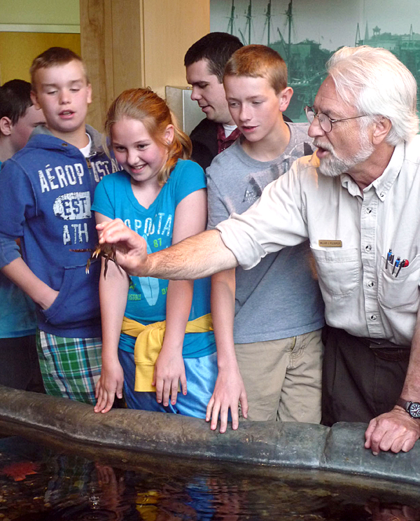 Dylan Howell, Willow Newman, and Ryan Howell, students at the Wabanaki Cultural Center, formerly the Downeast Heritage Museum, in Calais, get a hands-on lesson about a spider crab Friday from William Kolodnicki, U.S. Fish and Wildlife expert and director of the Moosehorn National Wildlife Refuge at Baring.
