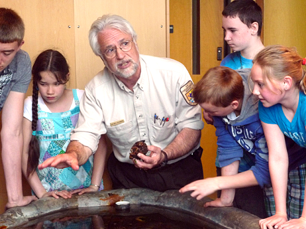 Students at the Wabanaki Cultural Center, formerly the Downeast Heritage Museum, in Calais, get a hands-on lesson about a sea cucumber Friday from William Kolodnicki, U.S. Fish and Wildlife expert and director of the Moosehorn National Wildlife Refuge at Baring.