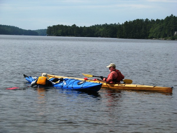 A couple practices kayak rescue/re-entry skills at a lake.