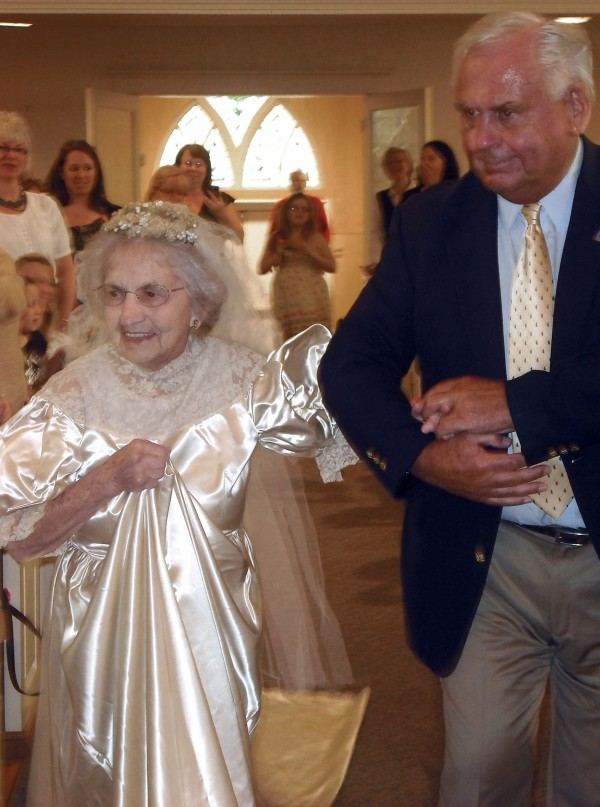 In this May 10, 2011 photo supplied by Kristi Fulton, Agnes Anderson, 98, of Laketon Township is escorted by her son, Dick Anderson, down the aisle of Samuel Lutheran Church, in Muskegon, Mich., during the church's vintage bridal gown fashion show.