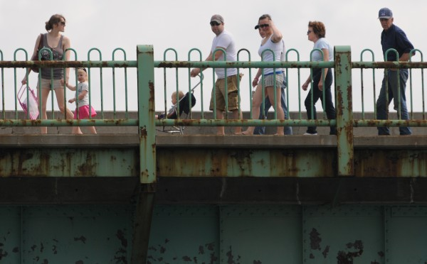 People crossing the Joshua Chamberlain Bridge on Monday watch as Bangor Fire personnel investigate the report of a body floating in the Kenduskeag Stream.