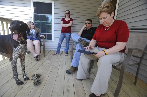 "On a computer tablet, Lynn Silk, far right,  looks at photos of her son, Staff Sgt. Brandon Silk, as she joined other family members on the family's back porch in Orono Friday, May 27, 2011. From left are family dog ""Koda"",  Brandon's cousin Katelynn Ronan, Brandon's sister-in-law, Jaclyn Silk, and Lynn Silk's husband Mark Silk. It has been nearly a year since the Silks lost Staff Sgt. Brandon Silk in a helicopter crash during his second deployment to Afghanistan."
