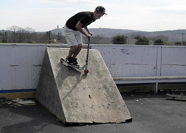 Dylan Sieber, 16, of Bucksport, uses a homemade ramp to do a trick on his scooter recently at a makeshift skate park that has been set up at the town's ice skating rink. A group of teens, backed by the town, hope to garner support from local residents to build new and expanded features for bikers, skateboarders and scooter riders.