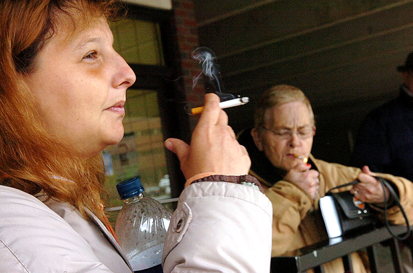 Crystal Fogleman (left), and Alice Goan (right), both of Bangor, smoke cigarettes as they wait for a bus in downtown Bangor on Monday. Both Fogleman, who started smoking at age eight and whose mother died of lung cancer, and Goan, who started smoking at age five, vehemently oppose the proposed $1.50 tax increase on cigarettes, the revenue of which would benefit the Fund for a Healthy Maine. &quotI think it's stupid. I've only got one vice and it's not going to make me stop,&quot stated Goan.