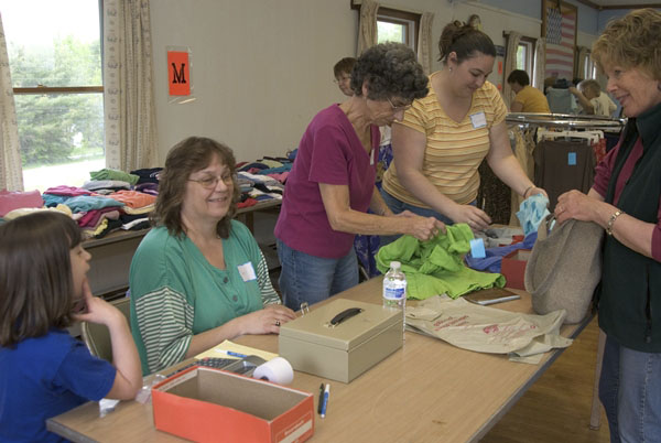 Four generations from one family took part in the 2010 Cash For Clothes event in Camden. They are (from left) Morgan Flanders, Cheryl Anderson, Emma Teel and Renee Flanders assisting shopper Diane Schelble. This year's event will take place Saturday, May 21, at the American Legion hall in Camden.