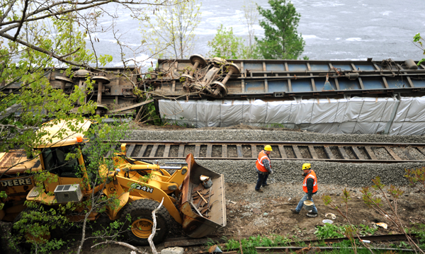 Railroad repair crew members pick up tools along the railroad tracks behind Eastern Maine Medical Center on Monday after replacing ties in in that area. Seven rail cars carrying sheet rock flipped on their side along the Penobscot River early Sunday morning spilling cargo towards the river.