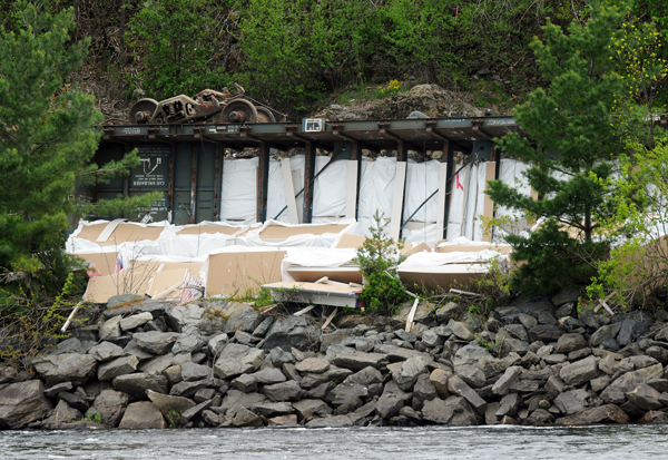 Seven rail cars carrying sheet rock flipped on their side along the Penobscot River early Sunday morning spilling cargo towards the river behind Eastern Maine Medical Center as seen on Monday. Railroad repair crews were seen replacing ties and shoring up tracks with crushed rock on Monday afternoon.