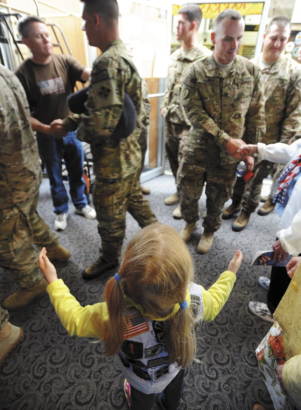 6 year-old Briana Fuhrer of Glenburn stands with out stretched arms awaiting hugs from armed forces members at Bangor International Airport on Saturday. Fuhrer and her family members were on hand to celebrate the 8th anniversary of the Maine Troop Greeters at the airport.