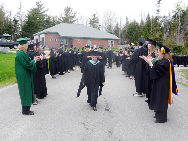 Graduating students at the University of Maine at Machias 100th graduation ceremony Saturday stand and applaud their instructors as they head into the commencement ceremonies.