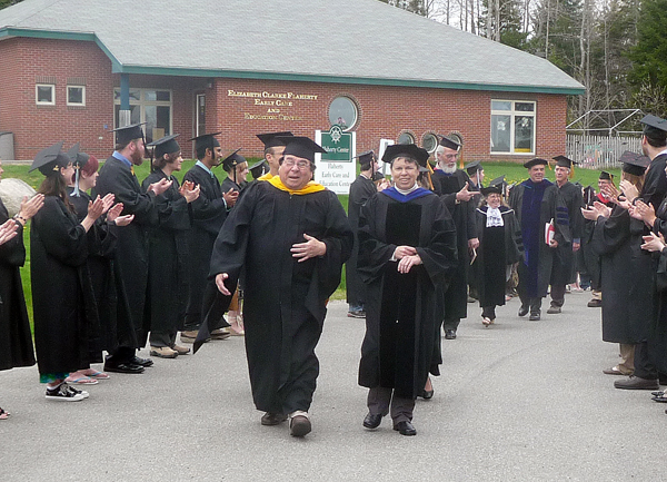 Graduating students at the University of Maine at Machias 100th graduation ceremony Saturday stand and applaud their instructors as they head into the commencement ceremonies.  Wayne Newell, University of Maine System board of trustees member (center, left), with UMM President Cynthia Huggins (center, right) smile as they march in a traditional faculty walk to the ceremonies.
