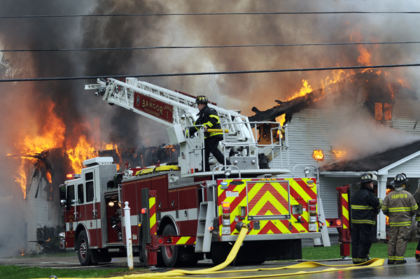 Bangor firefighters pull back and wait as the Calvary Apostolic Church in Winterport  burns on Thursday.