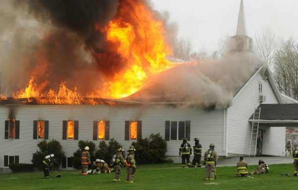 Firefighters from numerous departements pull back as the roof collapses on the Calvary Apostolic Church in Winterport on Thursday, May 5, 2011.