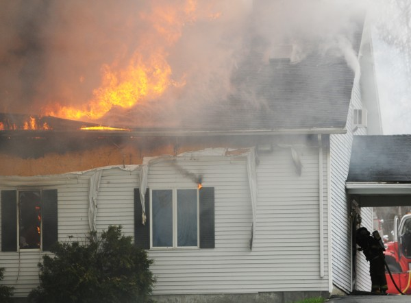 A firefighter peers into the front door of the Cavalry Apostolic Church in Winterport on Thursday, May 5, 2011.