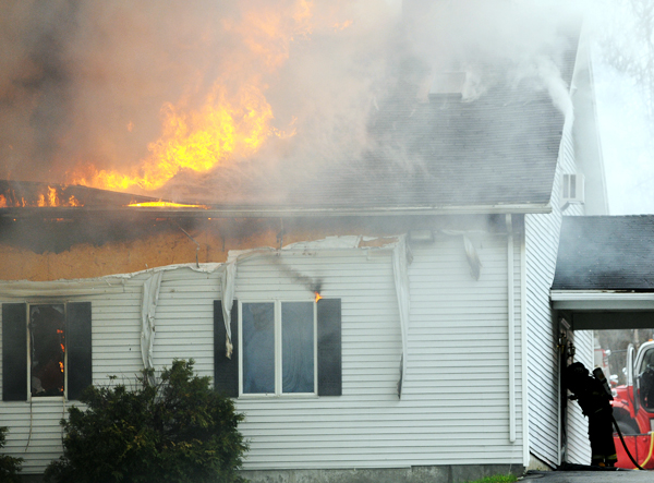 A firefighter peers into the front door of the Cavalry Apostolic Church in Winterport on Thursday.