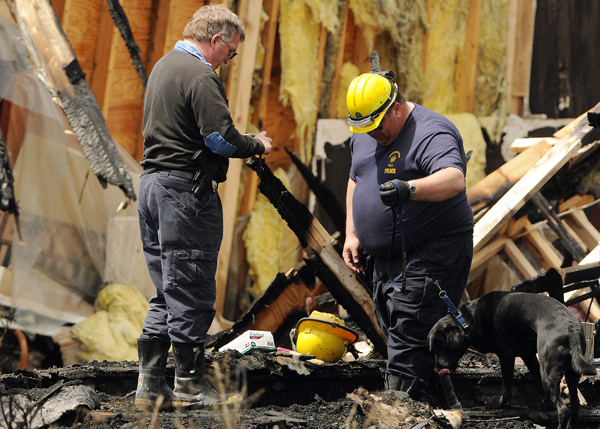 Officials with the Maine State Fire Marshal's Office investigate a fire at the Calvary Apostolic Church in Winterport on Friday.