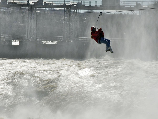 """Zip liner Virginia Nadeau hangs out over Grand Falls when a strong headwind cut short her ride across the gorge. """"I got to see the dam very close up,"""" Nadeau said."""