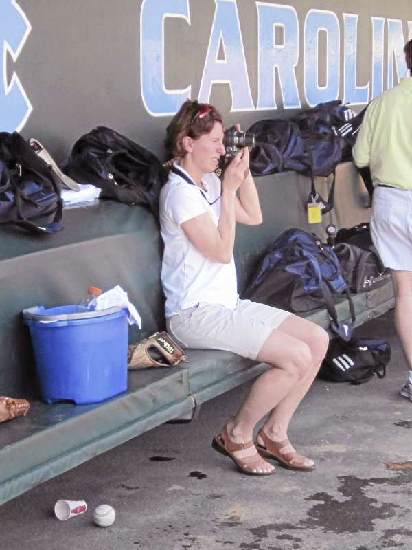 Lisa Trimper, the wife of UMaine baseball head coach Steve Trimper, snaps some photographs from the dugout during the Black Bears' Thursday afternoon practice session at Boshamer Stadium in Chapel Hill, N.C.