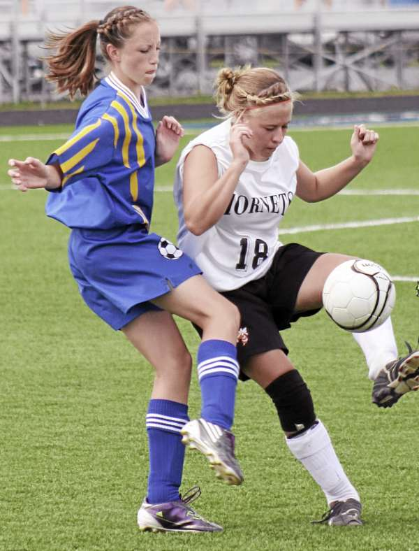 It has been a busy freshman season for Washburn's Carsyn Koch, who has played five varsity sports and has earned a letter in each. Koch (left) defends against Ashland's Brooke LaBelle during a soccer game last August. Koch will cap his fifth sport Saturday when she competes in the Class C state track and field championships in Bath.