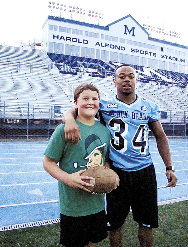 Roosevelt Boone (right) of the University of Maine poses with Will O'Neil of Orono, the son of faculty member Maryellen Mahoney-O'Neil, during a Black Bears football activity at Orono in 2010. Boone has started an organization called Strong Mind-Strong Body Inc. that is sponsoring a free Wellness and Nutrition Summer Youth Camp next month at UMaine.