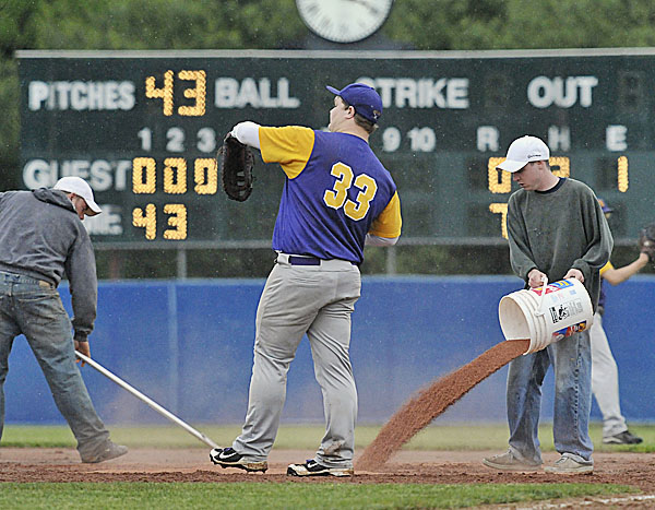 Mansfield Stadium groundskeeper Dana Leland rakes while Patrick Taylor pours more drying agent onto the area around first base as Bucksport's Shawn Smith (33) tries to get in a few throws at in the third  inning of the Eastern Maine Class B final against Waterville Tuesday at Mansfield Stadium in Bangor.
