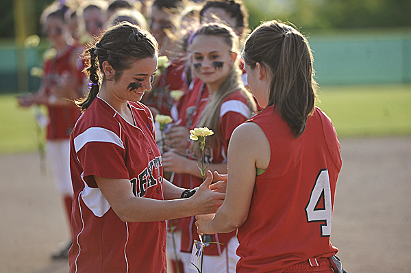 In memory of beloved  Dexter teacher Amy Lake, Central High School's Tabitha Goldsmith (4, right) joined her teammates in presenting yellow carnations to the Dexter High School team including  Harley Ponte, left, before their Class C  Eastern Maine softball final at Coffin field in Brewer Wednesday evening, June 15, 2011.